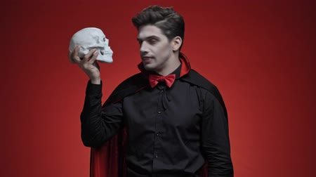 řev : Scary vampire man with fangs in black halloween costume holding human skull and turning it to the camera isolated over red wall