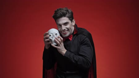 vampier : Scary vampire man with fangs in black halloween costume looking at human skull and roaring with it to the camera isolated over red wall