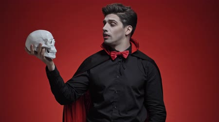 vampier : Scary vampire man with fangs in black halloween costume holding human skull and telling to it something isolated over red wall