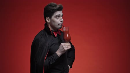 mystik : Glad vampire man with fangs in black halloween costume holding a tomato juice and drinking it with a cocktail tube isolated over red wall