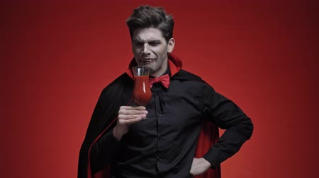 ijesztő : Scary vampire man with fangs in black halloween costume tasting a tomato cocktail and disliking it isolated over red wall
