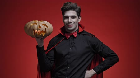vampiro : Vampire man with blood and fangs in black halloween costume congratulates with pumpkin in his hands isolated over red wall Stock Footage