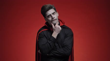 思考 : Mystic vampire man with blood and fangs in black halloween costume is thinking about something isolated over red wall 動画素材