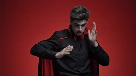 vampier : Vampire man with blood and fangs in black halloween costume is dancing and smiling isolated over red wall