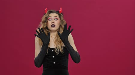 ruch : Pretty devil woman in carnival costume becoming scared and losing courage isolated over red wall background Wideo