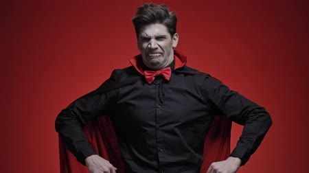 diabeł : Surprised vampire man with blood and fangs in black halloween costume becoming unhappy and angry because of getting bad news isolated over red wall Wideo