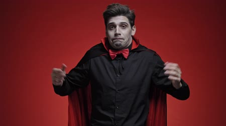 vampier : Vampire man with fangs in black halloween costume becoming confused and shrugging his shoulders isolated over red wall