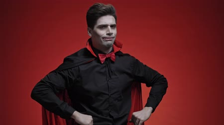 vampier : Handsome vampire man with fangs in black halloween costume shaking his head negatively isolated over red wall Stockvideo