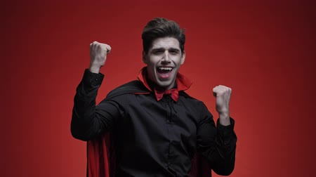 ijesztő : Happy vampire man with blood and fangs in black halloween costume looking at camera and making winner gesture isolated over red wall
