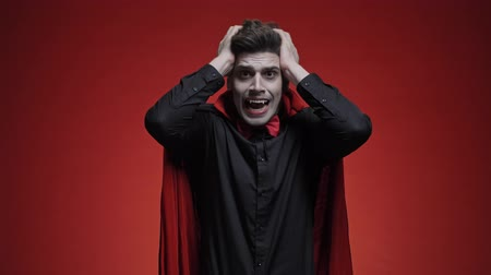 ijesztő : Vampire man with blood and fangs in black halloween costume touching his head and screaming because of getting bad news isolated over red wall