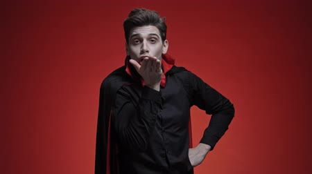 costumes : Vampire man with blood and fangs in black halloween costume blowing a kiss isolated over red wall