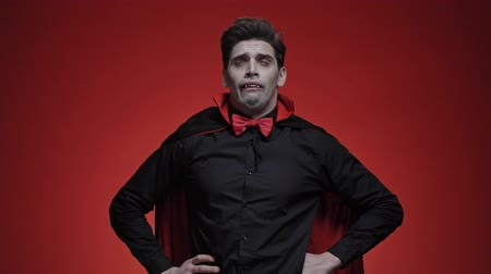 diabeł : Vampire man in black halloween costume is sneezing and losing his fangs isolated over red wall