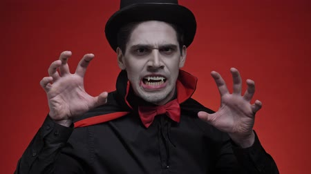 ijesztő : Scary vampire man with blood and fangs in black halloween costume attacking isolated over red wall