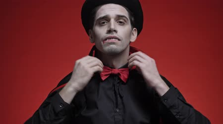 vampier : Attractive vampire man with blood and fangs in black halloween costume putting on his hat, fixing his bow tie and cloak isolated over red wall