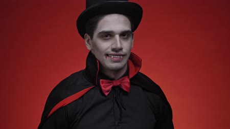 ruha : Scary vampire man with blood and fangs in black halloween costume is winking isolated over red wall