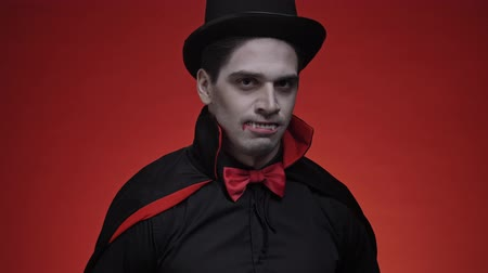řev : Vampire man with fangs in black halloween costume roaring and laughing isolated over red wall looking at the camera