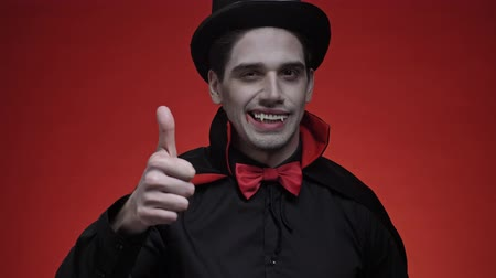 diabeł : Happy vampire man with blood and fangs in black halloween costume showing thumb up gesture isolated over red wall