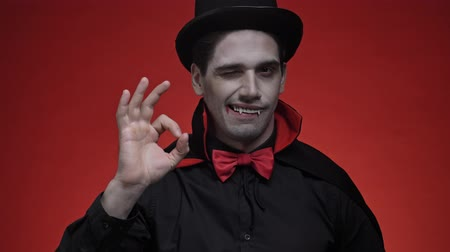 diabeł : Happy vampire man with blood and fangs in black halloween costume showing OK sign isolated over red wall