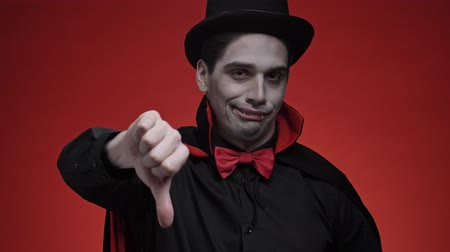vampier : Unhappy vampire man with blood and fangs in black halloween costume showing thumb down gesture isolated over red wall