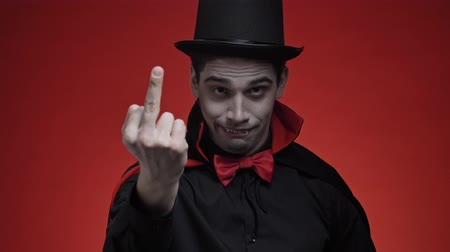 ruha : Scary vampire man with blood and fangs in black halloween costume showing middle finger isolated over red wall Stock mozgókép