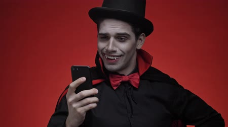 ijesztő : Vampire man with blood and fangs in black halloween costume waving with hand and laughing while having a video call on smartphone isolated over red wall Stock mozgókép