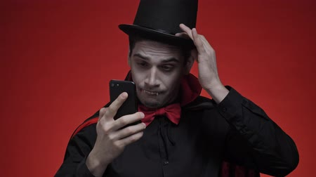 луки : Vampire man with blood and fangs in black halloween costume fixing his teeth, hat and tie while looking at smartphone isolated over red wall Стоковые видеозаписи