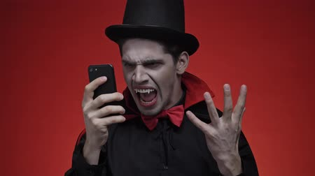 vampier : Vampire man with blood and fangs in black halloween costume becoming angry and screaming while using smartphone isolated over red wall