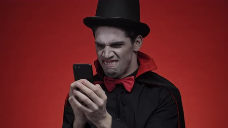 ijesztő : Angry vampire man with blood and fangs in black halloween costume grimacing while chatting on smartphone isolated over red wall