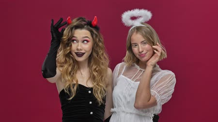 седые волосы : Angel and demon girls playing with hair and looking at the camera in carnival costumes isolated over red wall background