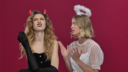 mascarada : Unhappy angel girl speaks with a demon girl and getting sad because demon girl does not listen her and covers her ears with fingers in carnival costumes isolated over red wall background