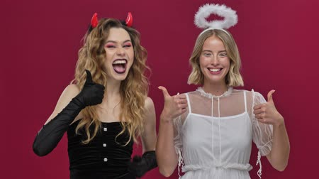 mascarada : Happy demon and angel girls with both hands show like gestures and look at the camera in carnival costumes isolated over red wall background