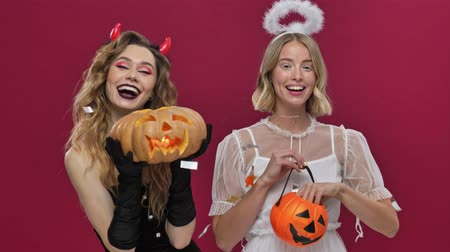 mascarada : Happy demon girl dancing with pumpkin in hands and angel girl smiling and throwing confetti from her pumpkin in carnival costumes isolated over red wall background