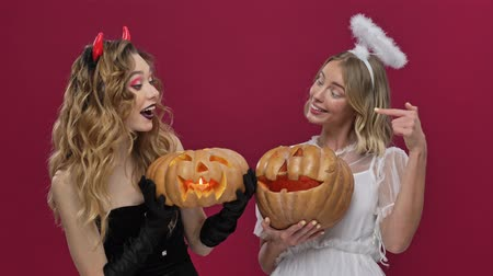 disputa : Pleased smiling demon and angel girls argue whose pumpkin is better and more beautiful in carnival costumes isolated over red wall background