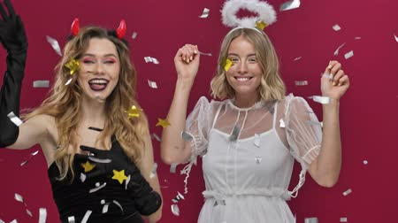 confettie : Happy smiling angel and demon girls throwing confetti and dancing in carnival costumes isolated over red wall background