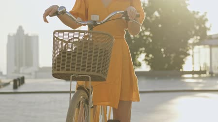 redhair : Cropped view of happy young redhead curly woman with bicycle smiling while standing outdoors at the street