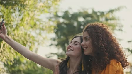 dinlenmek : Beautiful happy young girls friends gesturing and having fun while taking selfie photo on smartphone sitting in the park Stok Video
