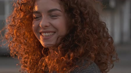 grimacing : Close up view of attractive cheerful young redhead curly woman in sweater smiling and grimacing while looking at the camera standing at the street