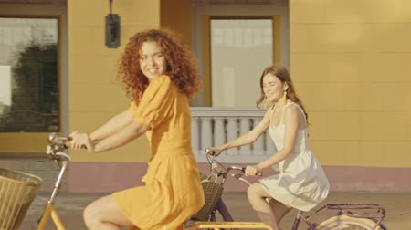 ciclo : Cheerful beautiful young girls friends smiling while riding on their bicycles outdoors at the street