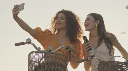 selfie girl : Cheerful cute young girls friends smiling and taking selfie photo on smartphone while sitting on their bicycles outdoors at the street