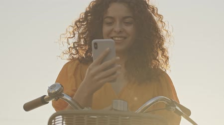 roodharige : Cheerful young redhead curly woman smiling and using smartphone while sitting on her bicycle outdoors at the street