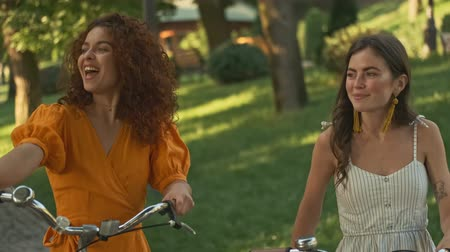hóquei : Cheerful pretty young girls friends looking at someone and waving with hand while walking with bicycles outdoors in the park Stock Footage
