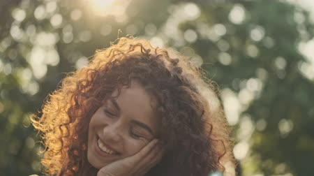 close cropped : Attractive flirty young redhead curly woman smiling and looking at someone to the side while standing in the park