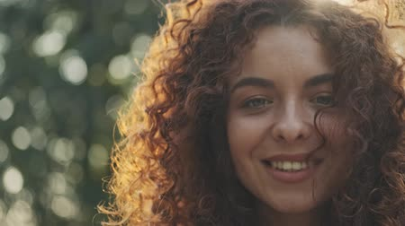 shy girl : Close up view of charming flirty young redhead curly woman smiling and looking around while resting in the park Stock Footage