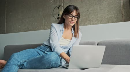írás : Attractive young business woman smiling and working on laptop while sitting on sofa at home