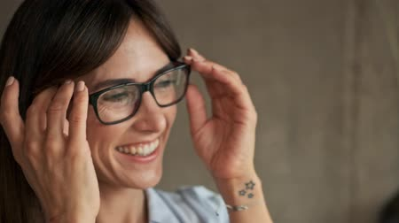 dinlenmek : Close up view of cheerful cute young business woman taking her eyeglasses off and feeling a little tired while working at home