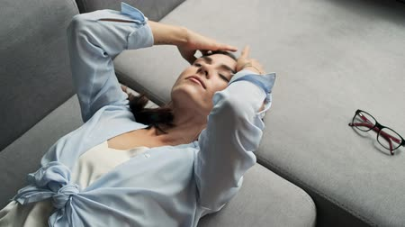 flat head : Top view of attractive calm young business woman resting with closed eyes and fixing her hair with hands while lying on sofa at home