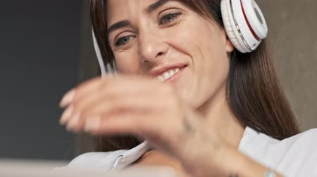 close cropped : Cropped view of happy cute young woman smiling and touching her chin with hand while listening music with wireless headphones sitting indoors at home Stock Footage