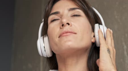 закрытыми глазами : Close up view of beautiful calm young woman smiling with closed eyes and listening music with wireless headphones while sitting indoors at home