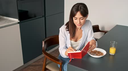 flocos de milho : Attractive young woman writing in her notebook and having a breakfast while sitting at kitchen in the morning Stock Footage