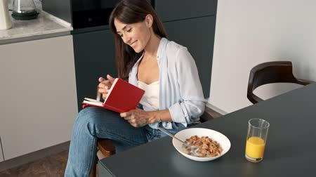 примечание : Excited young woman writing in her notebook and having a breakfast while sitting at kitchen in the morning Стоковые видеозаписи